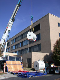 An MRI machine being hoisted into a building by a crane.